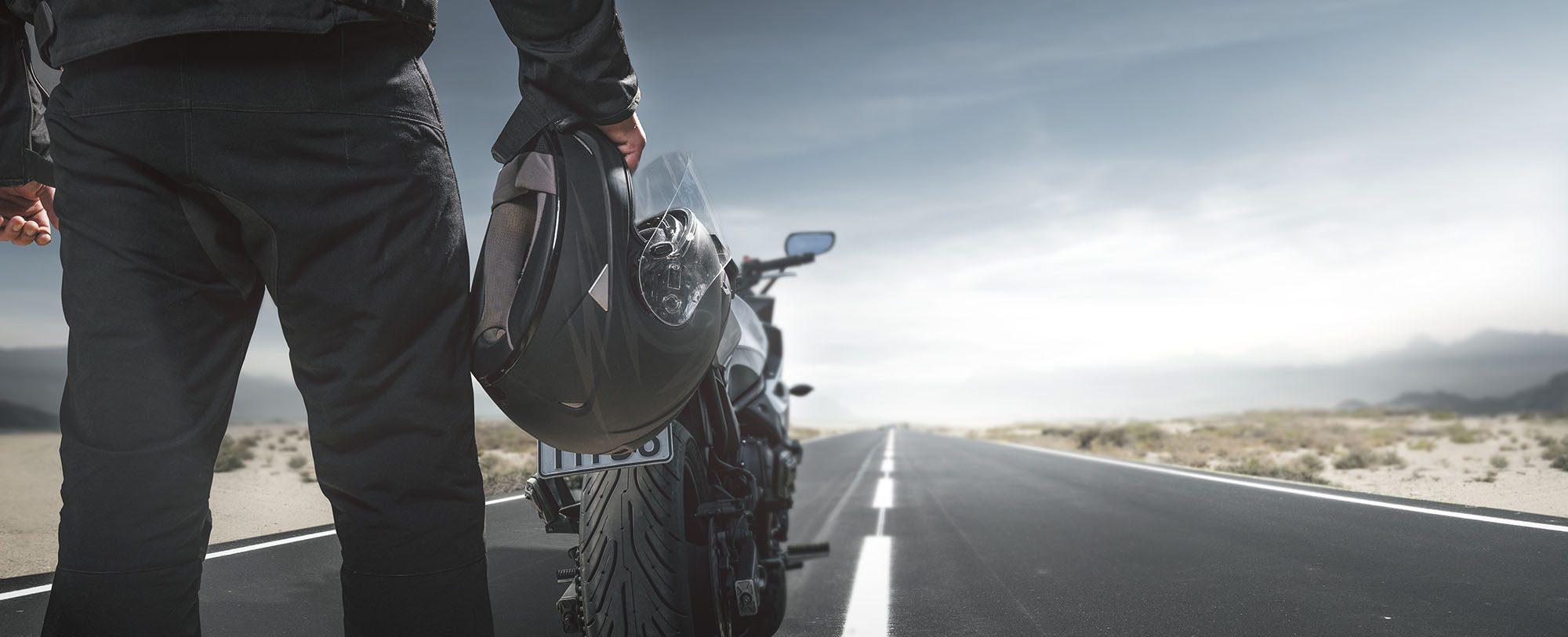 Biker mit Motorrad auf einer Landstraße